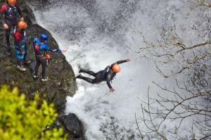 Photo of man jumping into a waterfall.