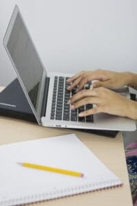 Hands at a laptop keyboard with notepad nearby
