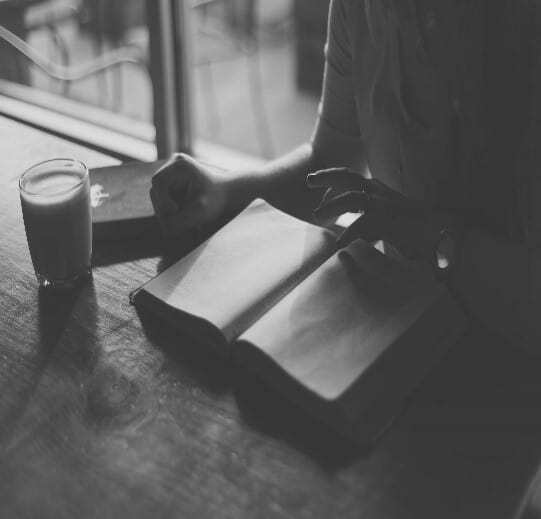Person reading a book with a cup of coffee